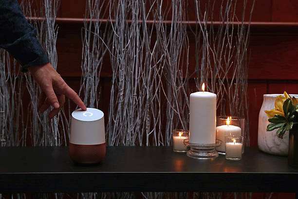 figure touching Google Home on a table near candles