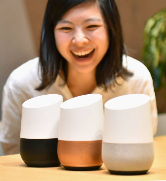 woman laughing looking a 3 Google Home smart speaker