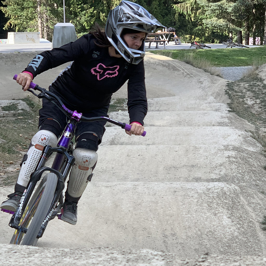 biking girl on pump track looking to corner