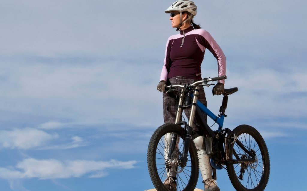 woman and a mountain bike looking in the horizon
