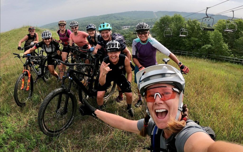 a group of women with their mountain bikes taking a group picture