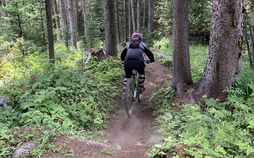 a woman going downhill on her mountain bike